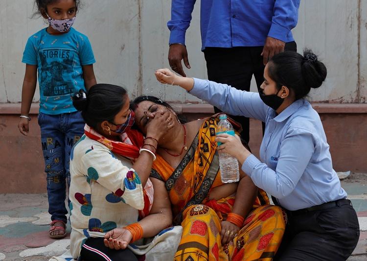 Một phụ nữ ngất đi sau khi nghe tin chồng qua đời vì Covid-19 ở New Delhi ngày 15/4. Ảnh: Reuters.