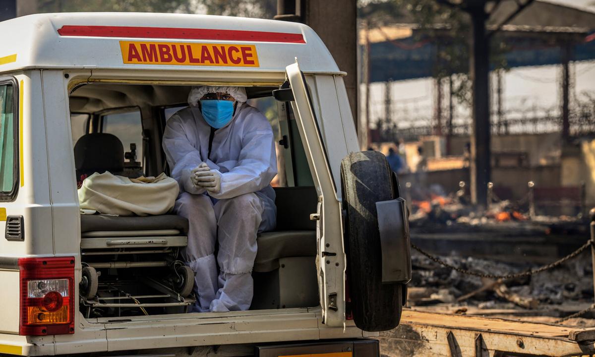 Người đàn ông ngồi chờ tới lượt hỏa táng cho người thân bên ngoài khu hỏa táng ở New Delhi. Ảnh: NYTimes.