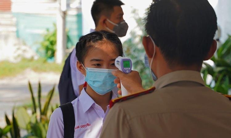 Học sinh Lào đeo khẩu trang, kiểm tra thân nhiệt khi tới trường học ở thủ đô Vientiane hồi tháng 6/2020. Ảnh: UNICEF.