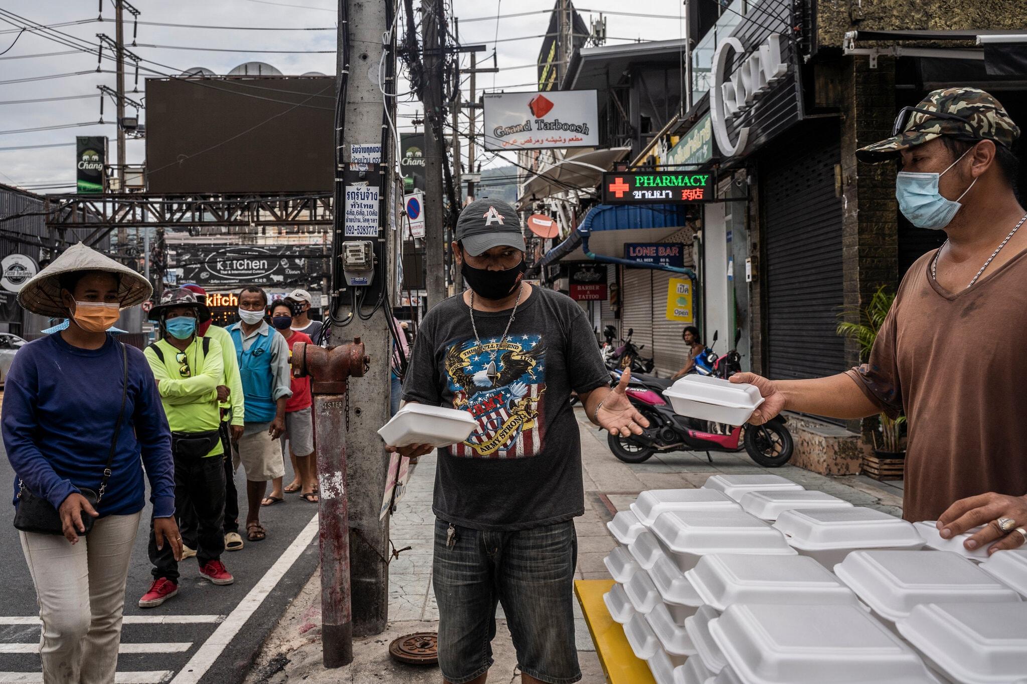Tình nguyện viên phát các phần ăn tại phố đi bộ Bangla ở Phuket vào tháng này. Ảnh: NYTimes.