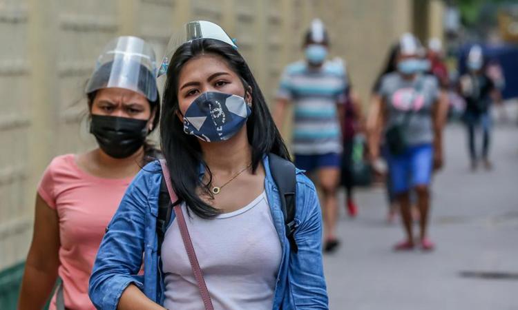 Người dân đeo khẩu trang và mặt nạ chống giọt bắn trên đường phố Manila, Philippines hôm 15/4. Ảnh; Xinhua.
