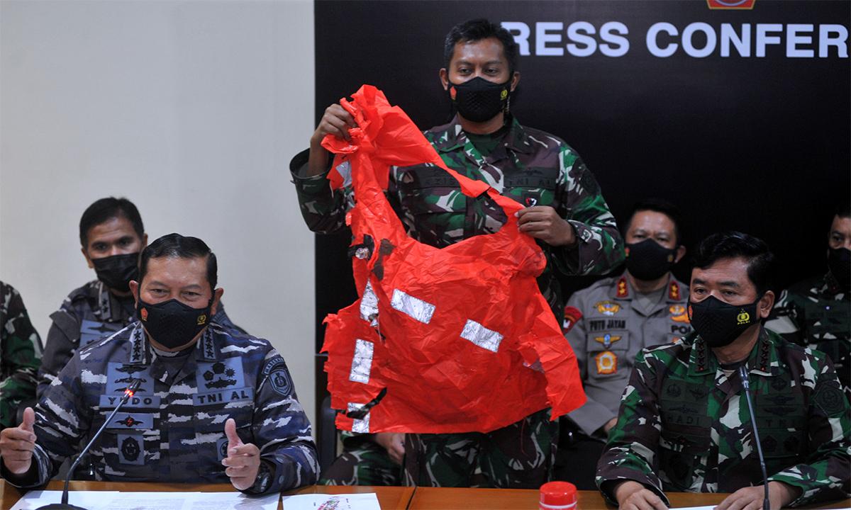 Binh sĩ Indonesia cầm áo phao được cho là của tàu ngầm KRI Nanggala trong cuộc họp báo ở Bali ngày 25/4. Ảnh: Reuters.