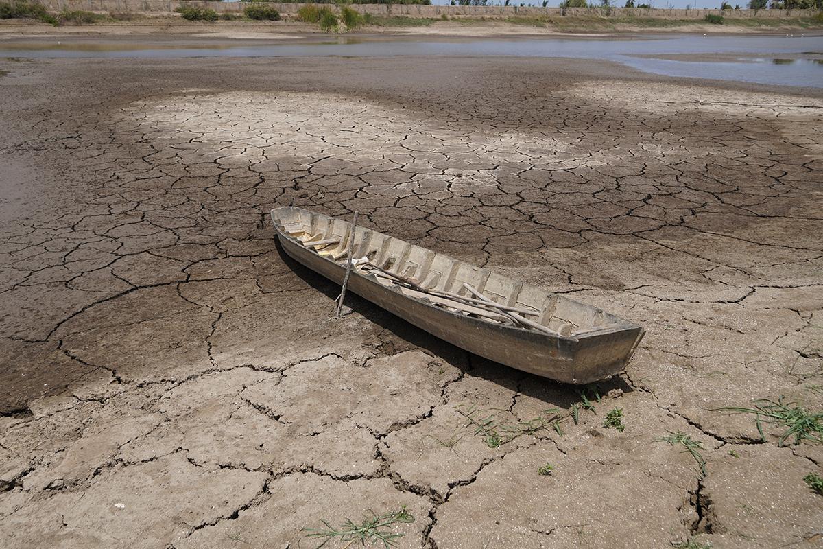Một chiếc xuồng người dân dùng giăng câu lưới nằm chỏng chơ giữa lòng hồ cạn nước. Ảnh: Hoàng Nam