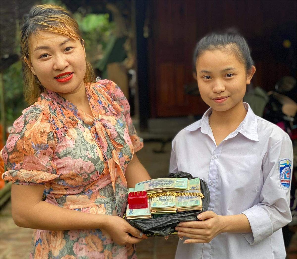 Mỹ Dung (góc phải) cùng chị Thắm, bên số tiền và trang sức nhặt được. Ảnh: Hùng Lê