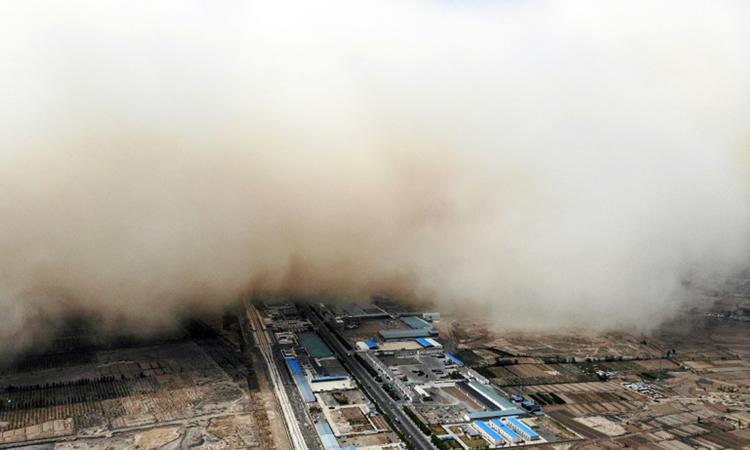 Bức tường cát khổng lồ bao phủ thị trấn ở huyện Lâm Trạch, thành phố Trương Dịch, tỉnh Cam Túc hôm 25/4. Ảnh: AFP.
