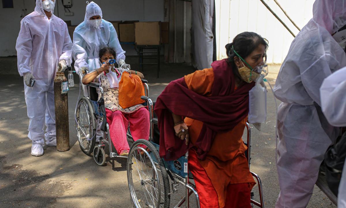 Nhân viên y tế hỗ trợ bệnh nhân Covid-19 bên ngoài một trung tâm cách ly ở Mumbai hôm 27/4. Ảnh: Bloomberg.