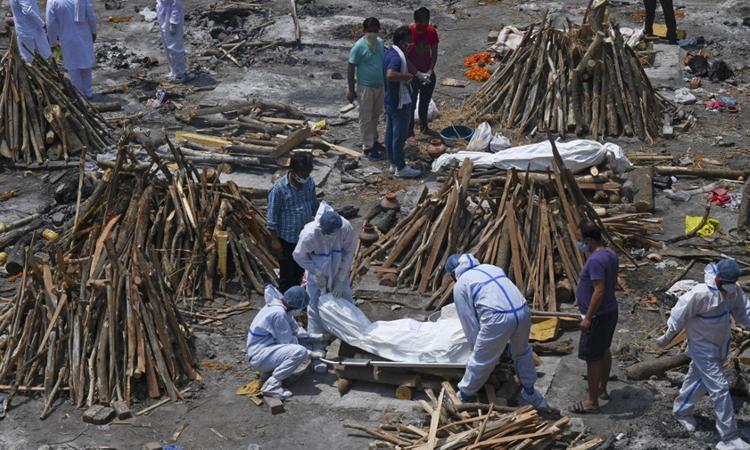 Các thành viên gia đình và nhân viên xe cứu thương mặc đồ bảo hộ khiêng thi thể nạn nhân chết Covid-19 tại một khu hỏa táng ở New Delhi, Ấn Độ hôm 27/4. Ảnh: Reuters.