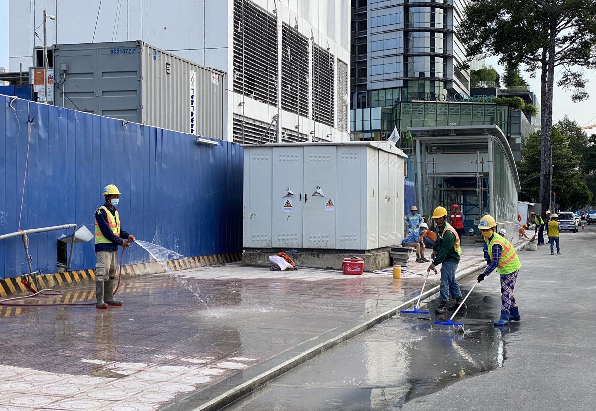 Công nhân dọn dẹp công trường Metro Số 1 trên đường Lê Lợi, chiều 28/4. Ảnh: Gia Minh.