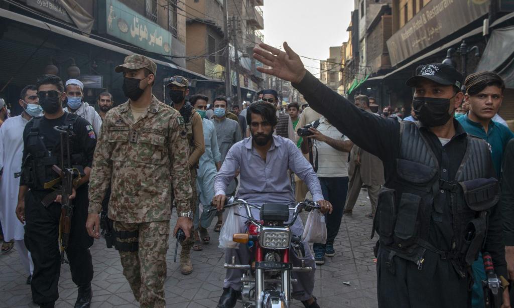 Binh sĩ và cảnh sát tuần tra một khu chợ nhằm đảm bảo thực thi các biện pháp chống Covid-19 tại thành phố Peshawar, Pakistan, hôm 26/4. Ảnh: AFP.