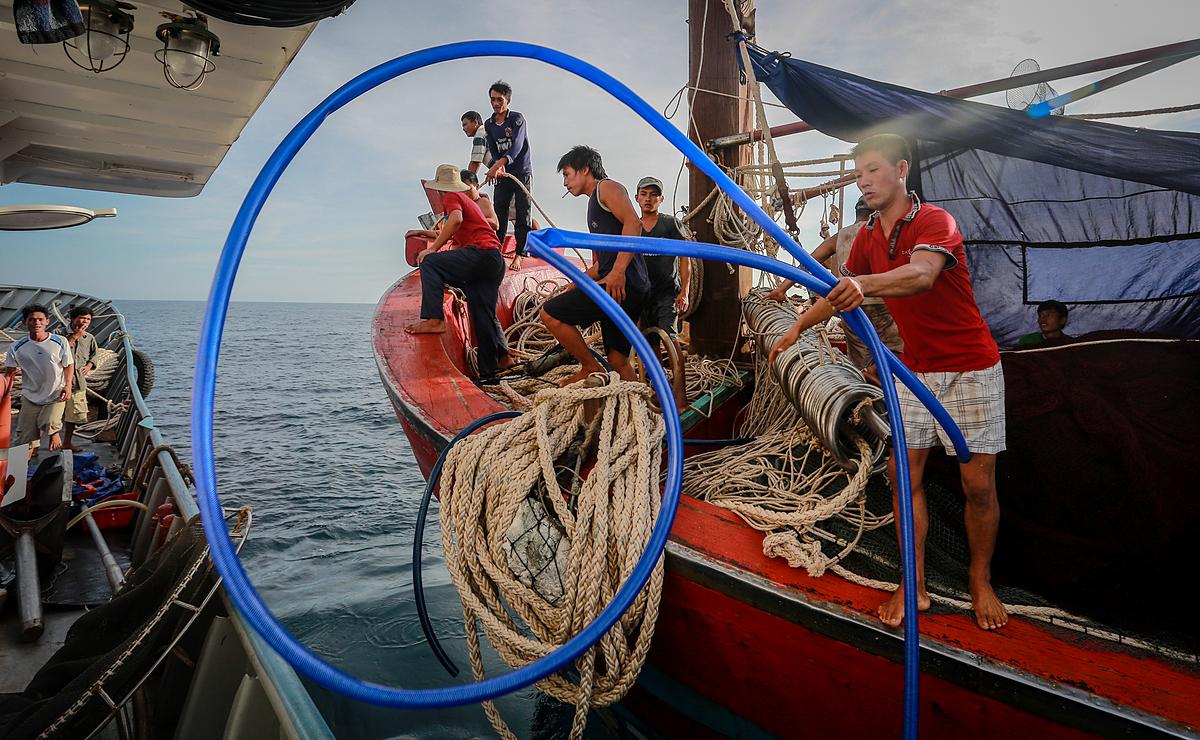 Một thuyền viên tàu cá Quảng Bình mang ống nước xin nước ngọt từ tàu cá Sang Fish 01 trên vùng biển vịnh Bắc Bộ. Ảnh: Nhung Nguyễn.