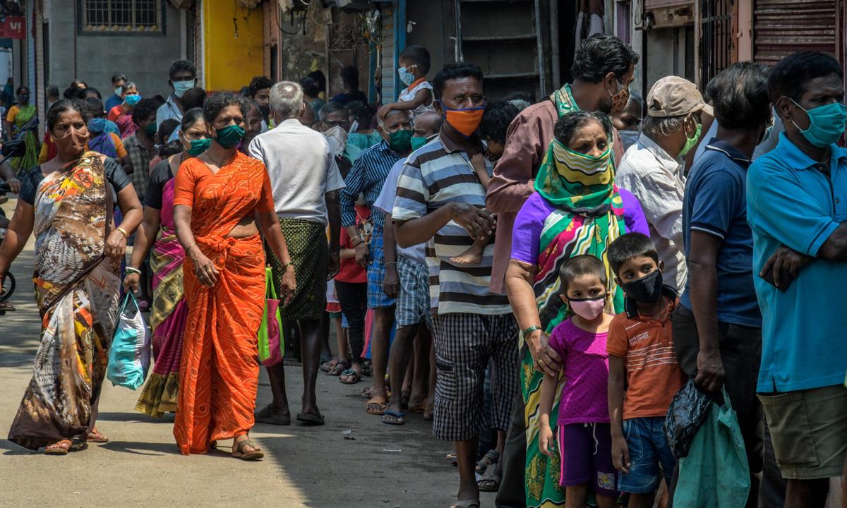 Người dân xếp hàng nhận trợ cấp lương thực tại Dharavi, thành phố Mumbai hồi đầu tháng này. Ảnh: NYTimes.