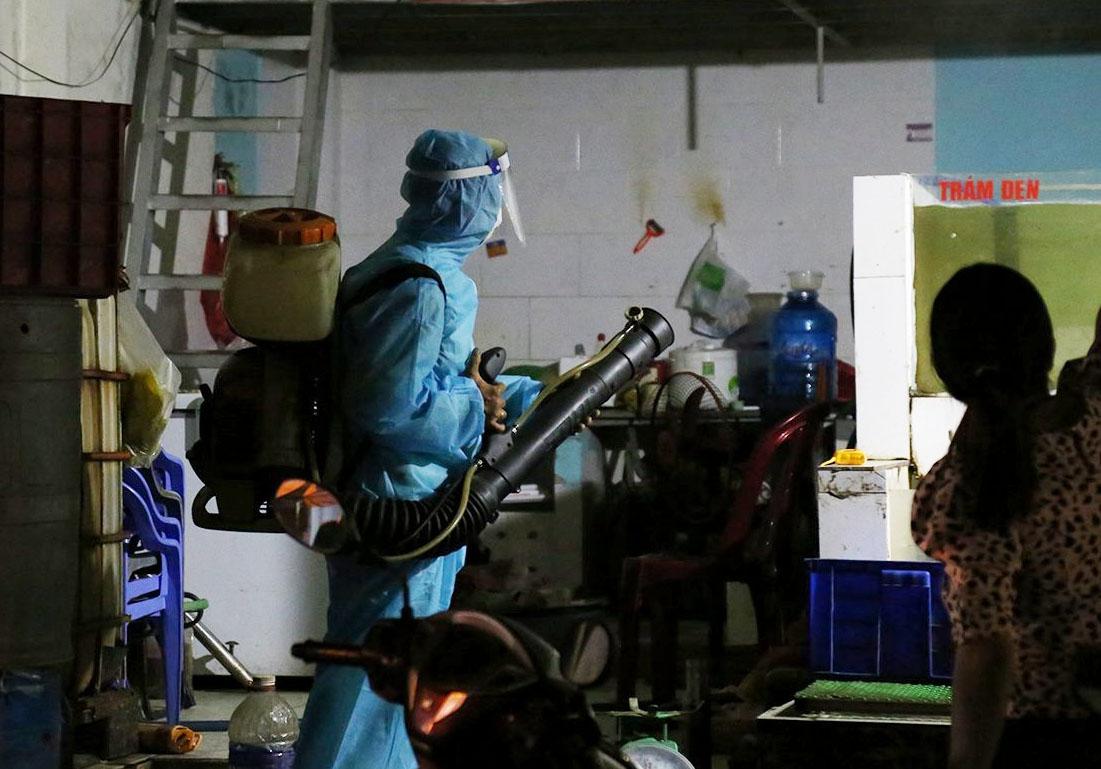 Nhân viên y tế phun khử trùng toàn bộ phòng trọ, tối 29/4. Ảnh: Đình Văn.