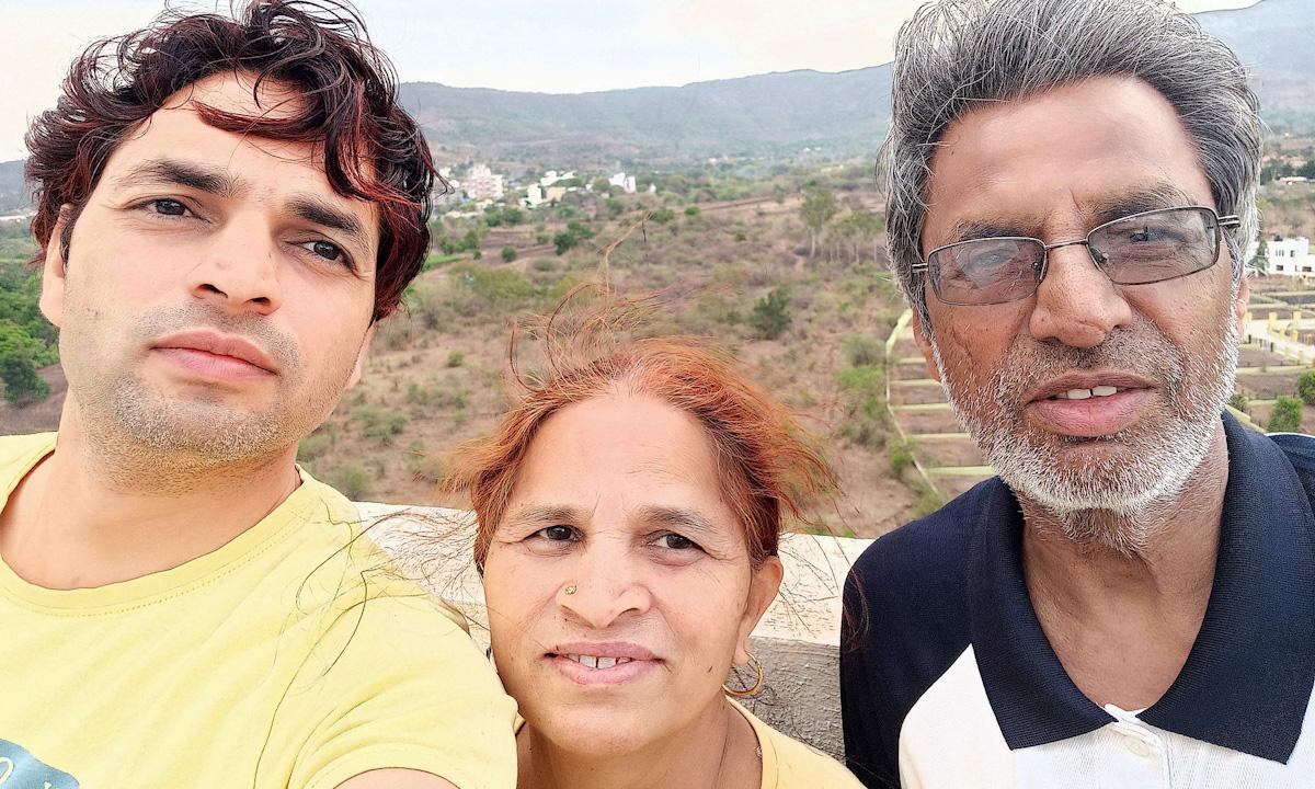 Ajay Koli (trái) chụp ảnh cùng bố mẹ tại Ấn Độ. Ảnh: NYTimes.
