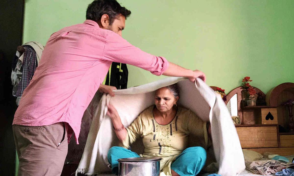 Ajay Koli xông người cho mẹ tại nhà ở New Delhi cuối tháng trước. Ảnh: NYTimes.