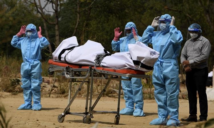 Người thân mặc đồ bảo hộ cầu nguyện trước thi thể nạn nhân Covid-19 được chôn cất tại một nghĩa địa ở New Delhi, Ấn Độ hôm 30/4. Ảnh: AFP.