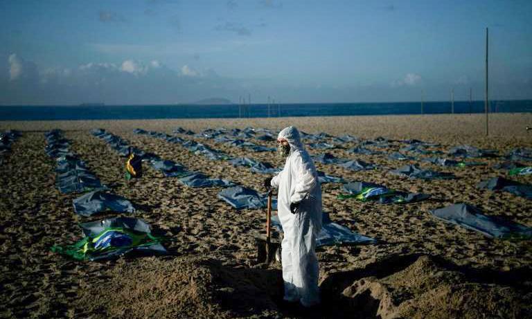 Một người đàn ông đào mộ tượng trưng để biểu tình phản đối cách xử lý Covid-19 của chính phủ ở bãi biển Copacabana, thành phố Rio de Janeiro tháng trước. Ảnh: AFP.