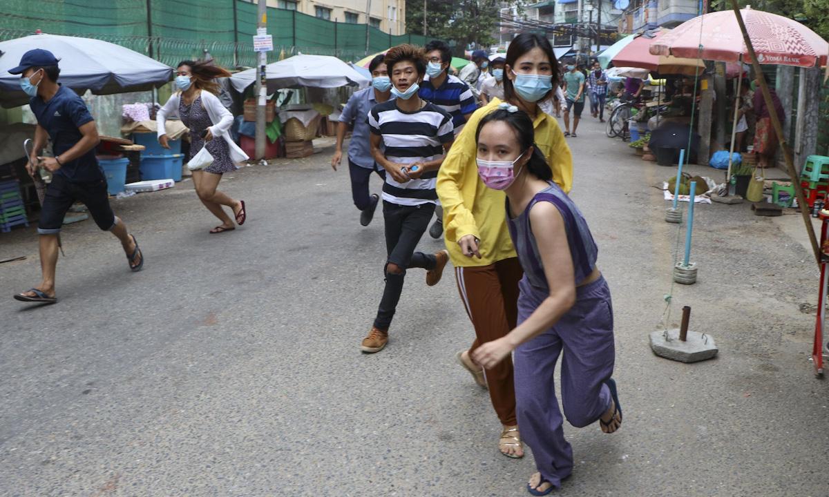 Người biểu tình chống đảo chính chạy trốn cảnh sát và binh lính ở thành phố Yangon hôm 27/4. Ảnh: AP.