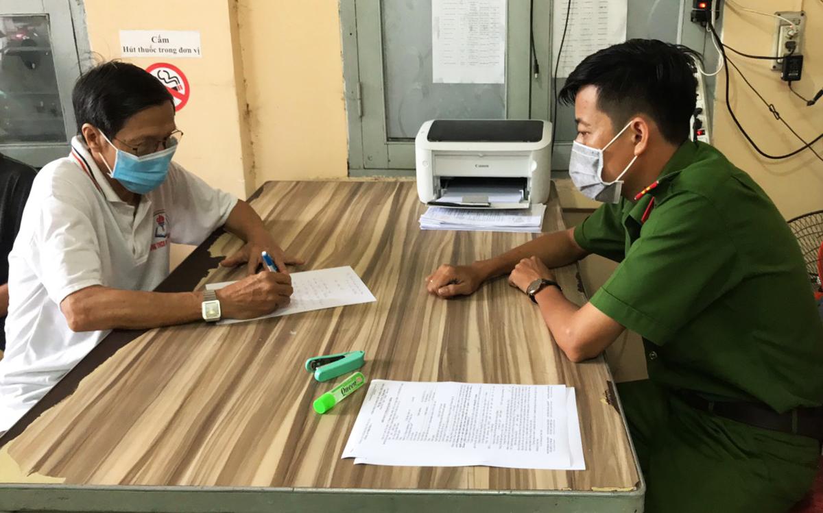 Công an Phường 1, TP Vũng Tàu làm việc với người đàn ông không đeo khẩu trang nơi công cộng, sáng 3/5. Ảnh: Quang Bình.