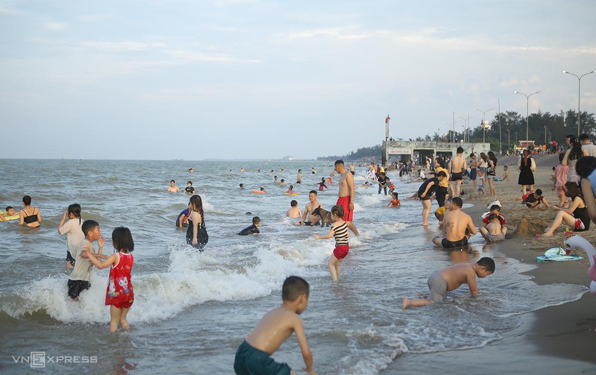 Nhiều người tắm mát, ngồi nghỉ ở bãi cát không đeo khẩu trang, chiều 2/5. Ảnh: Nguyễn Hải