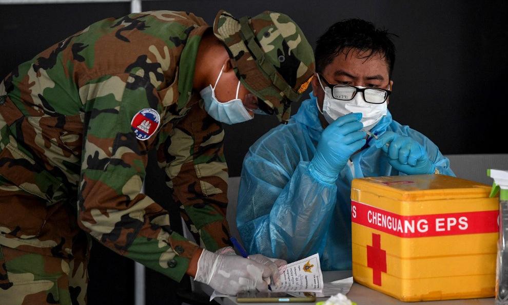 Binh sĩ Campuchia hỗ trợ nhân viên y tế chuẩn bị tiêm vaccine Covid-19 tại điểm tiêm chủng ở thủ đô Phnom Penh ngày 1/5. Ảnh:AFP.