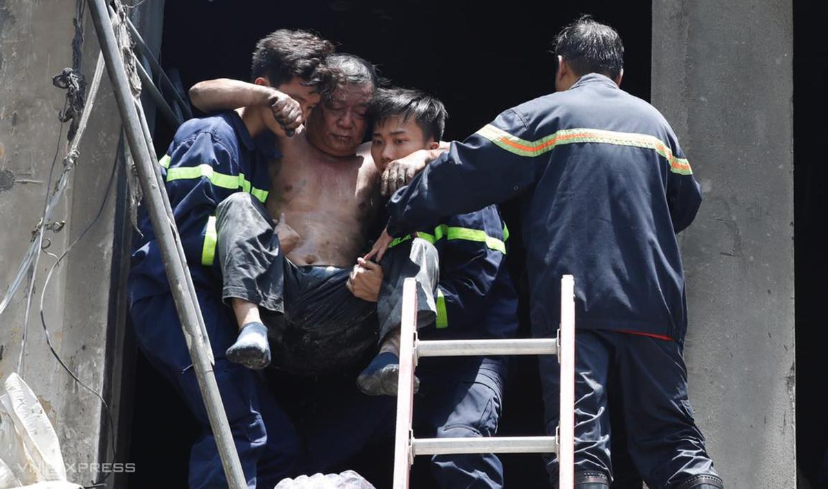 Ông Lợi bị bỏng, ám khói đen khắp người được cảnh sát giải cứu từ phòng vệ sinh ở lầu 1. Ảnh: Hữu Khoa.