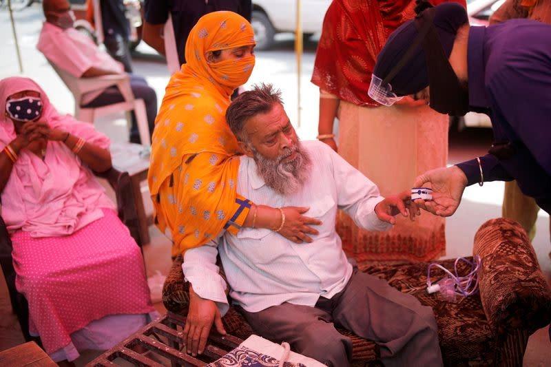 Một tình nguyện viên đo nồng độ oxy trong máu một người đàn ông trước khi hỗ trợ ông thở oxy miễn phí tại đền Sikh ở Ghaziabad, ngoại ô New Delhi, hôm 3/5. Ảnh: Reuters