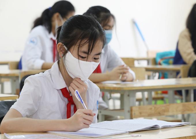 Học sinh trường THCS Nguyễn Du (Nam Từ Liêm, Hà Nội) đeo khẩu trang, đo nhiệt độ trong ngày trở lại trường đầu tiên sau nhiều tháng nghỉ học năm 2020. Ảnh: Ngọc Thành.