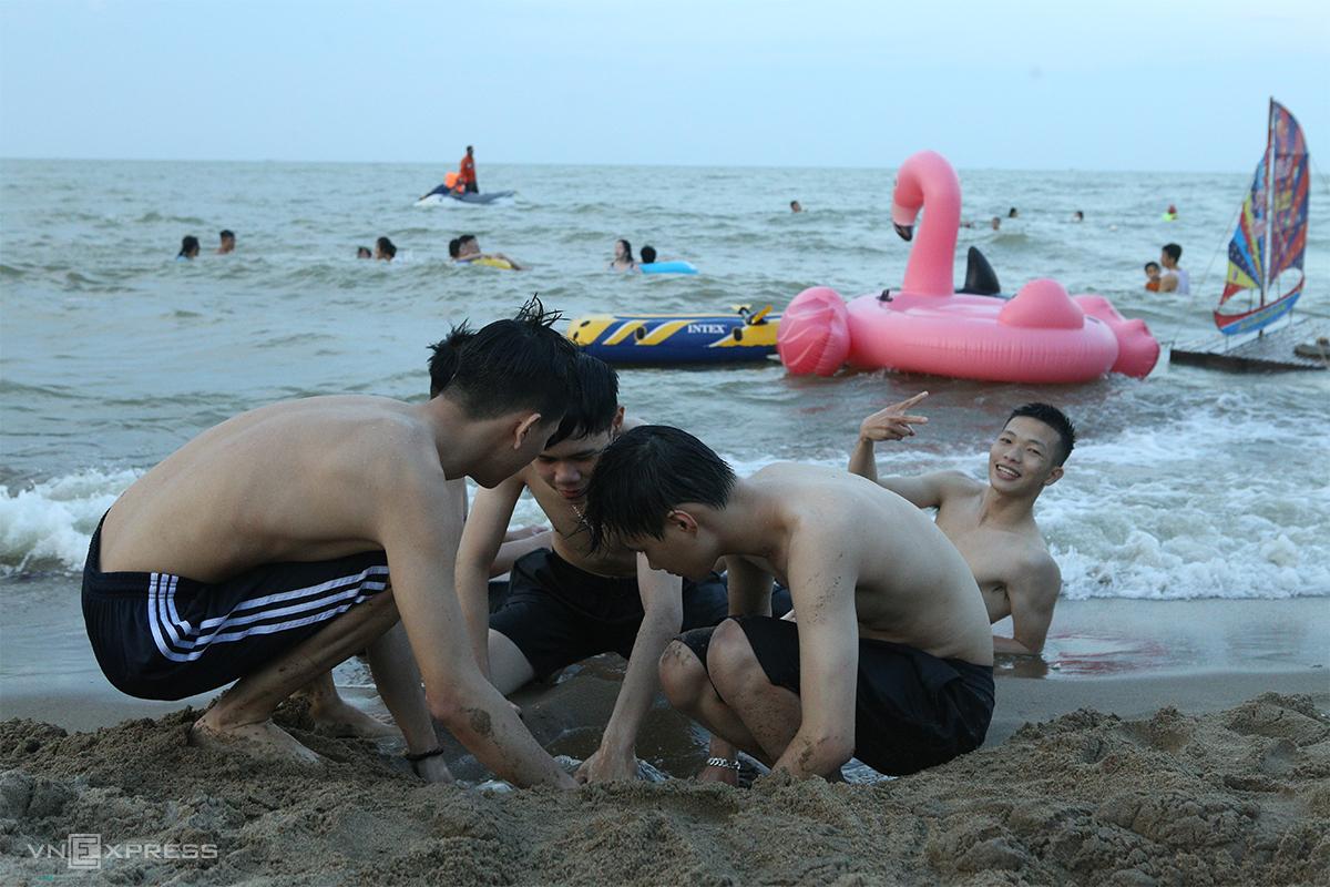 Nhiều tốp thanh niên ngồi sát sát nhau đùa chơi tại bãi tắm. Ảnh: Nguyễn Hải