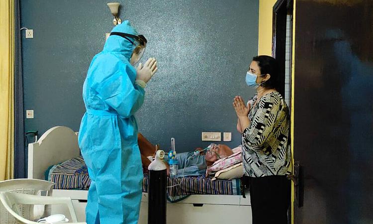 Một tình nguyện viên thuộc Hội Thanh niên Ấn Độ hướng dẫn cách sử dụng bình oxy. Ảnh: NY Times.