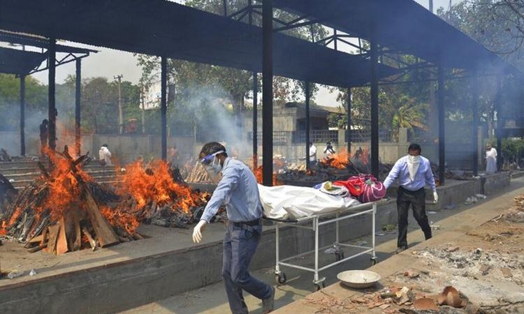 Thân nhân chuyển thi thể của bệnh nhân Covid-19 vào một lò hỏa táng ở New Delhi, Ấn Độ, hôm 1/5. Ảnh: AP.