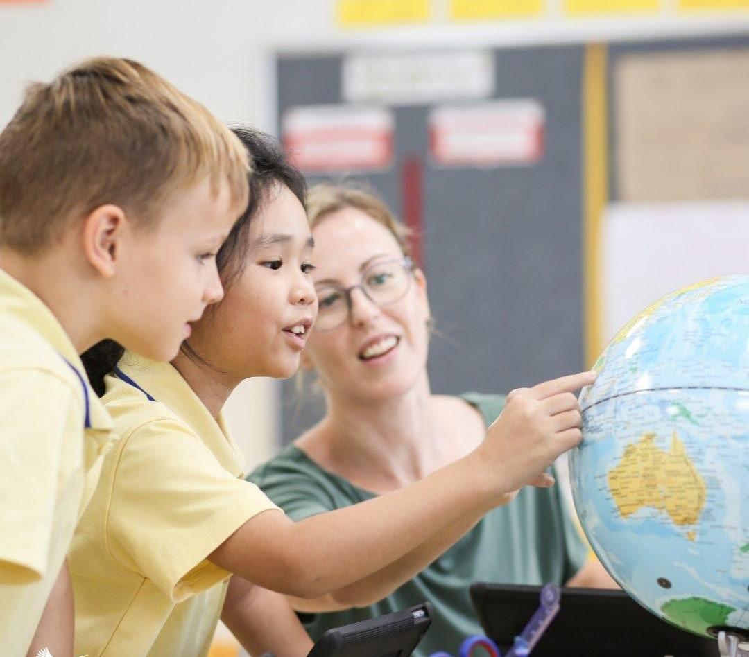 Giáo viên nước ngoài giảng dạy học sinh tiểu học về bản đồ thế giới trong chương trình Tú tài Quốc tế.
