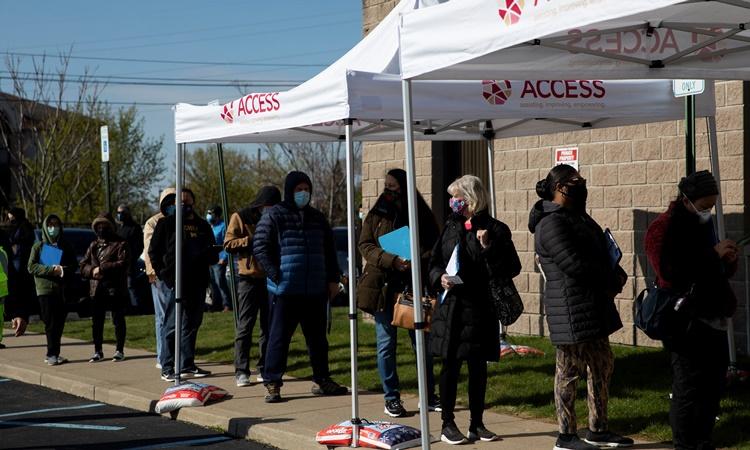Người dân xếp hàng chờ tiêm vaccine Covid-19 tại một điểm tiêm chủng ở Dearborn, Michigan, ngày 22/4. Ảnh: Reuters.
