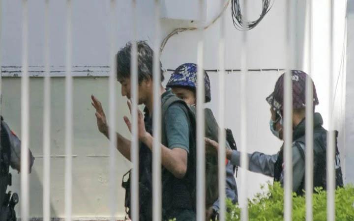 Phóng viên Nhật Yuki Kitazumi bị áp giải tới đồn cảnh sát Myaynigone ở thị trấn Sanchaung, Yangon, hôm 26/2. Ảnh: AP.