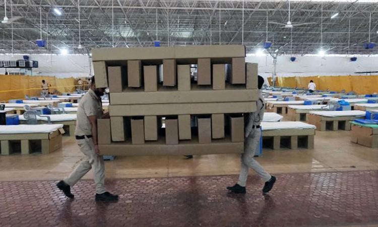 Nhân viên khiêng giường bệnh làm từ bìa các tông tại cơ sở điều trị Covid-19 Sardar Patel, ngoại ô New Delhi hôm 24/4. Ảnh: Bloomberg.