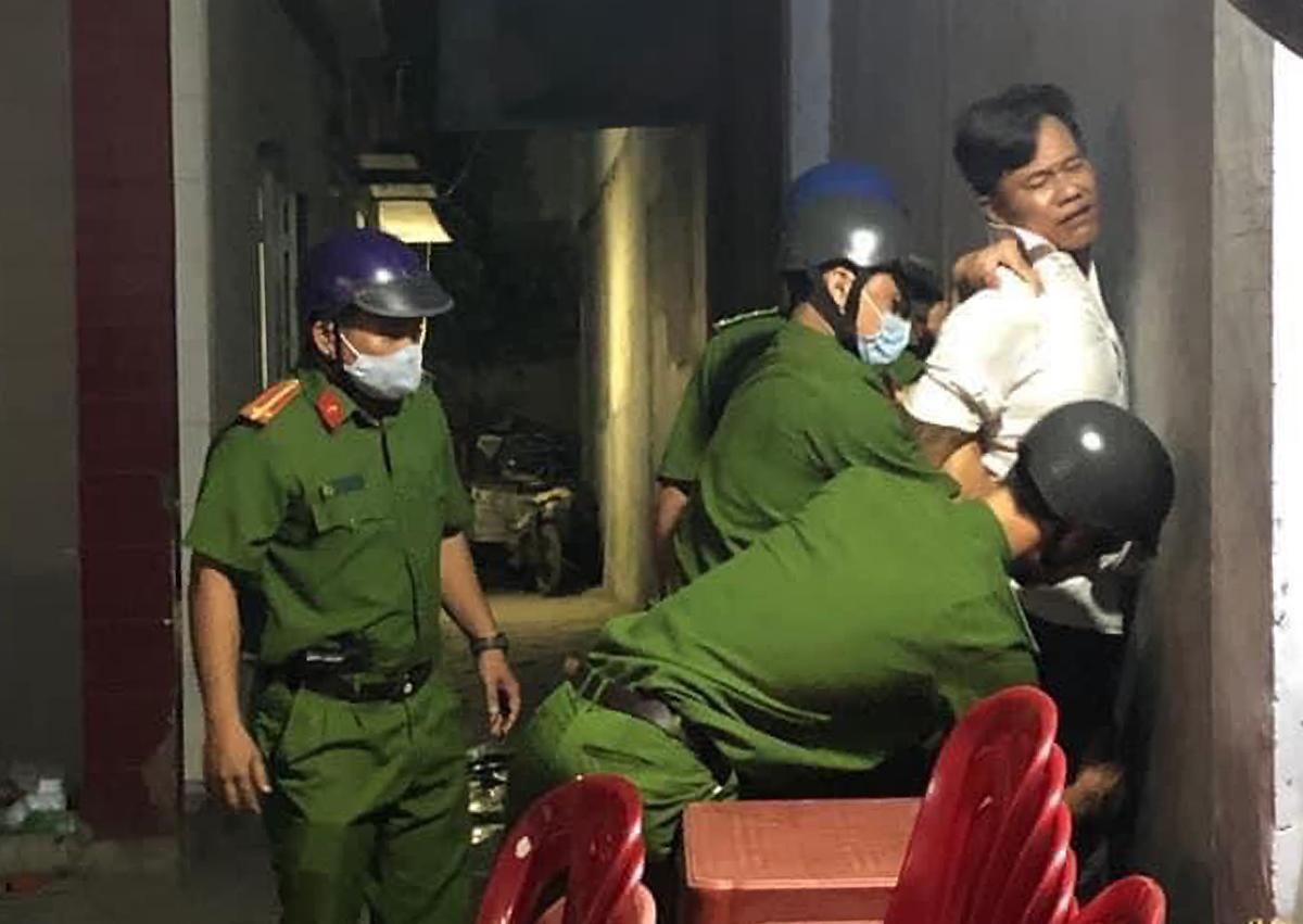 Tánh (áo trắng) bị cảnh sát khống chế. Ảnh: Người dân cung cấp.