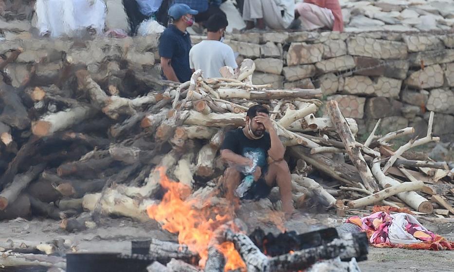 Các thành viên gia đình tập trung gần nơi hỏa táng người thân qua đời vì Covid-19 tại thành phố Allahabad, Ấn Độ, hôm 4/5. Ảnh: AFP.