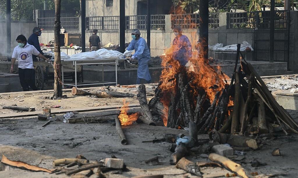 Người thân đẩy một chiếc cáng đưa thi thể một nạn nhân Covid-19 đến giàn thiêu tại một khu hỏa táng ở New Delhi vào ngày 5/5. Ảnh: AFP.