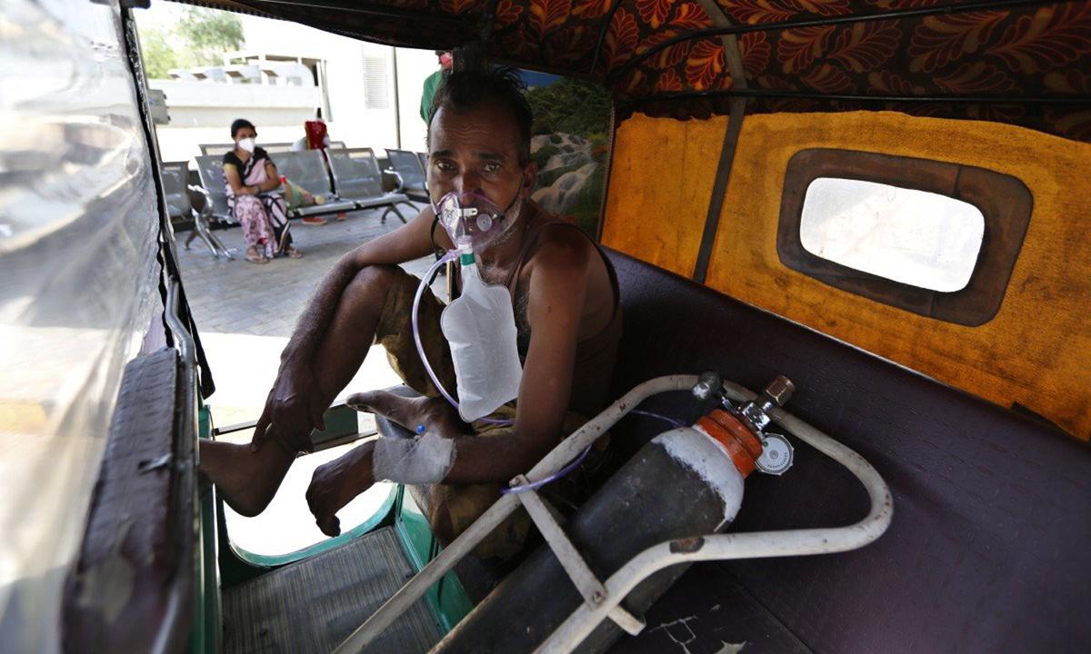 Một bệnh nhân Covid-19 thở oxy trên xe kéo trong khi chờ nhập viện ở Ahmedabad tháng trước. Ảnh: AP.