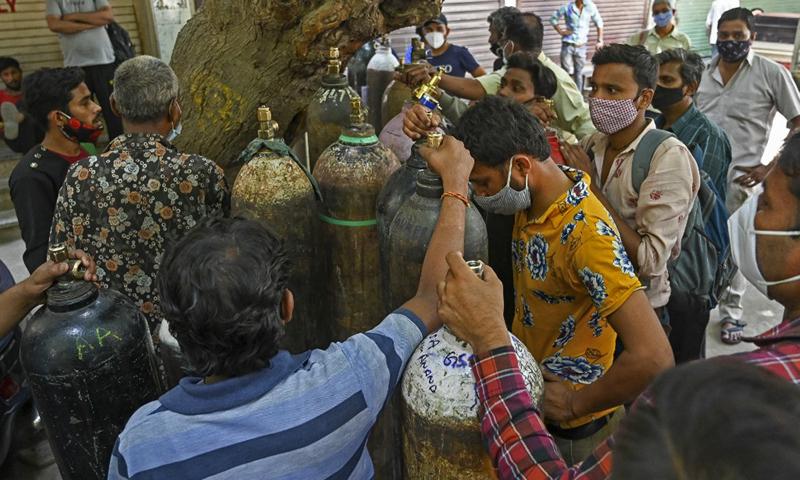 Người dân chờ nạp bình oxy y tế cho bệnh nhân Covid-19 điều trị tại nhà tại một trung tâm nạp oxy tư nhân ở New Delhi, Ấn Độ hôm 4/5. Ảnh: AFP.