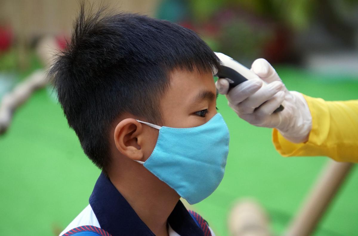 Học sinh trường tiểu học Nguyễn Bỉnh Khiêm (quận 1, TP HCM) được đo thân nhiệt khi vào trường. Ảnh: Mạnh Tùng.