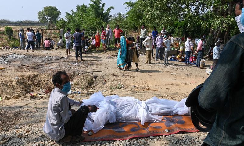 Một người thân ngồi cạnh thi thể giáo viên chết vì Covid-19 tại lò hỏa táng ở thành phố Moradabad, bang Uttar Pradesh, Ấn Độ hôm 5/5. Ảnh: AFP.
