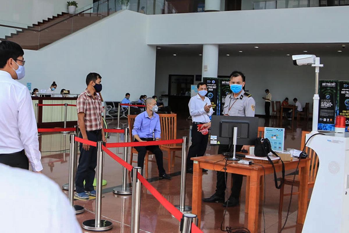 Người ra vào Trung tâm hành chính Đà Nẵng được kiểm tra thân nhiệt, giữ khoảng cách và đeo khẩu trang. Ảnh: Đông Khanh.