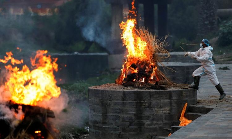 Nhân viên tang lễ mặc đồ bảo hộ hỏa thiêu thi thể bệnh nhân Covid-19 ở Kathmandu, Nepal, hôm 3/5. Ảnh: Reuters.
