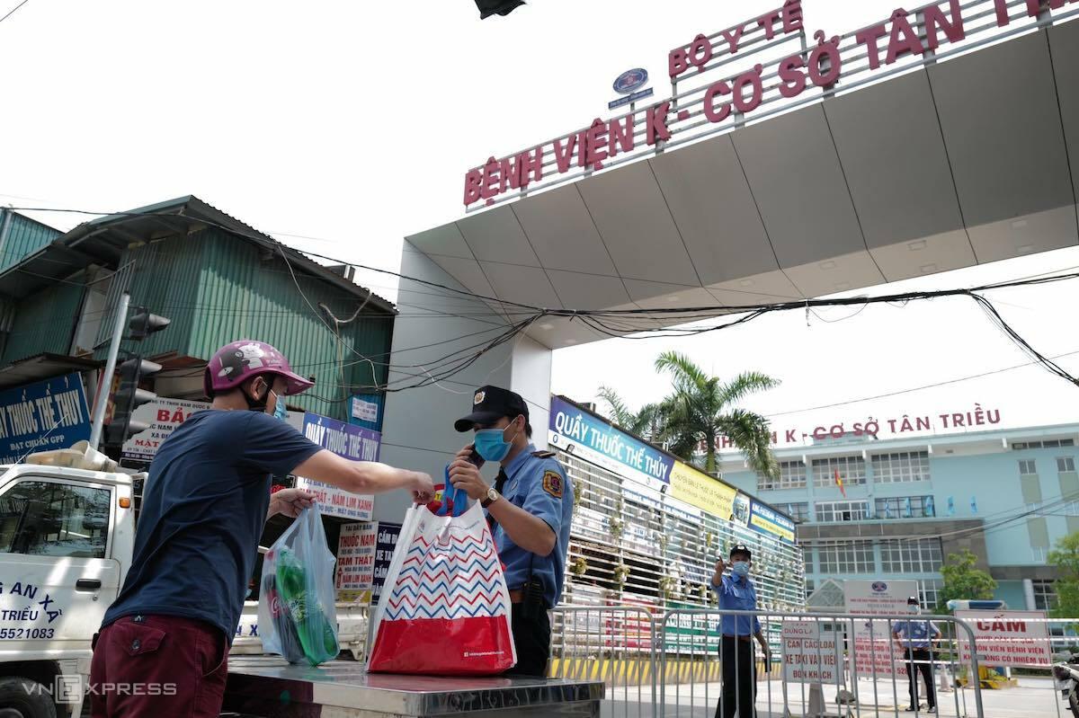 Người nhà chuyển nhu yếu phẩm cho bệnh nhân qua bảo vệ chốt chặn ở cổng Bệnh viện K. Ảnh: Ngọc Thành