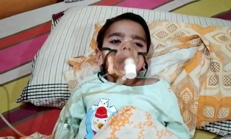 Con trai giáo sư đại học Alok Kumar đeo mặt nạ dưỡng khí nằm tại nhà riêng ở New Delhi ngày 5/5. Ảnh: CNN.