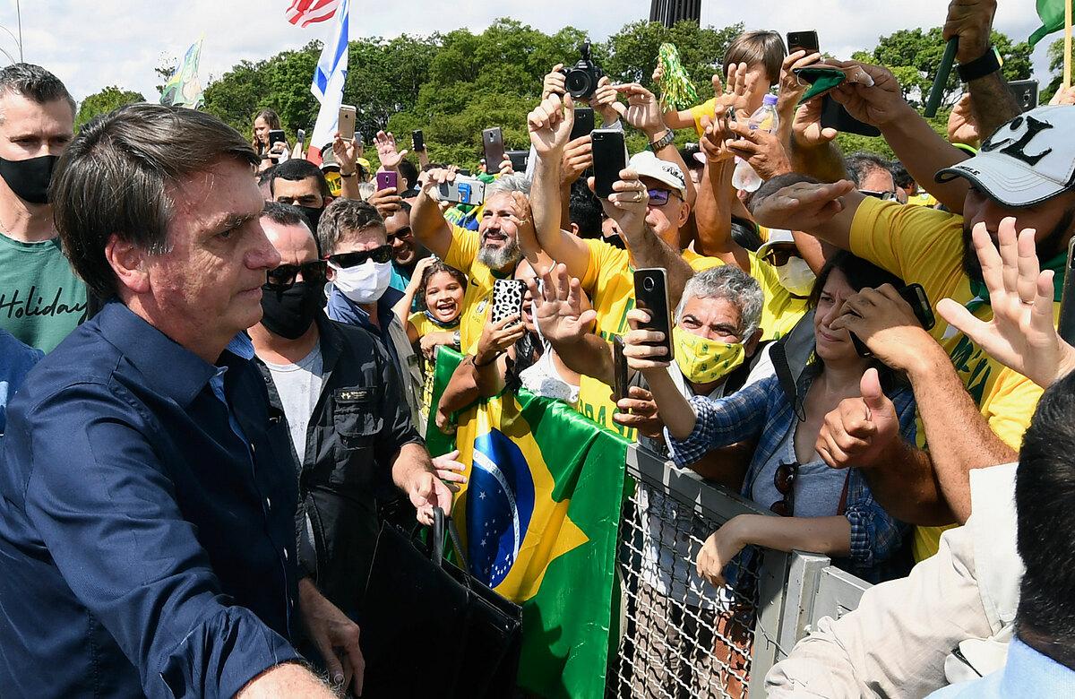 Tổng thống Bolsonaro (trái) tiếp xúc người dân tại Dinh Planalto ở Brasilia, ngày 24/5/2020. Ảnh: AFP.