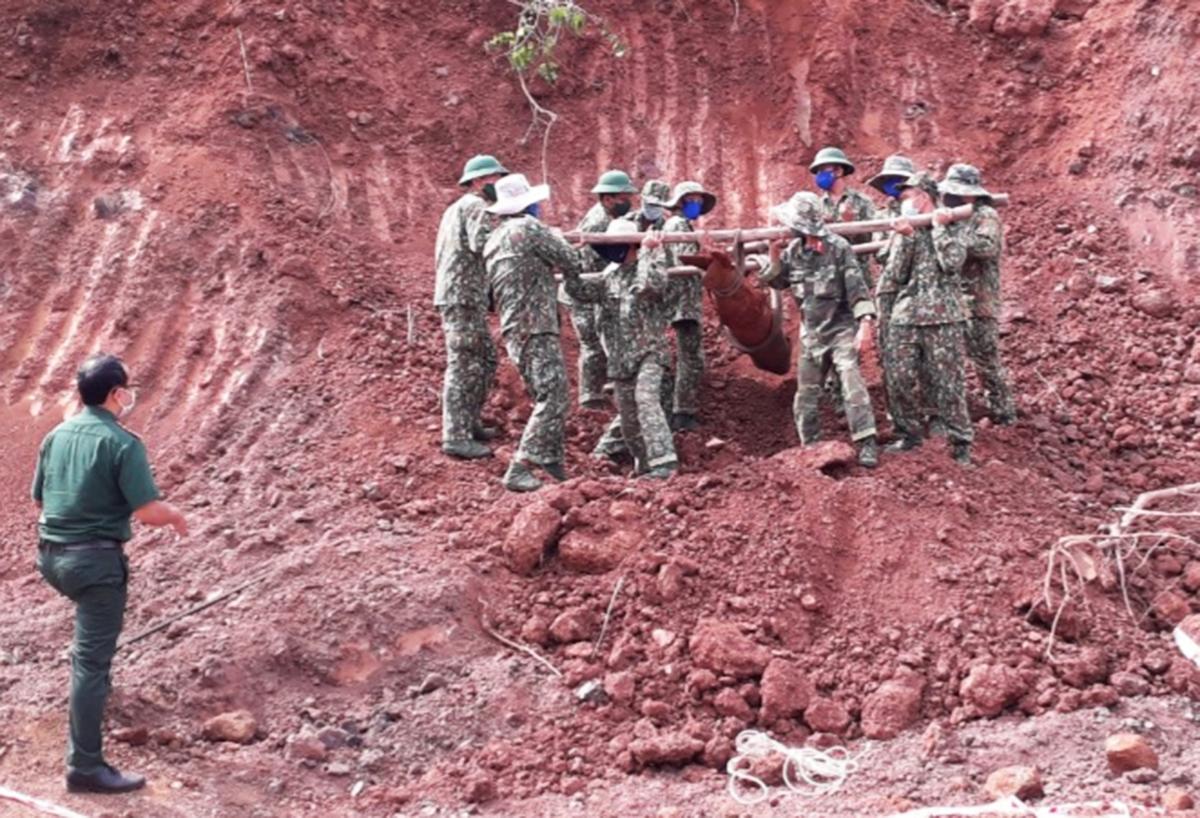 Bộ đội công binh khiêng quả bom ra khỏi vị trí được phát hiện. Ảnh: Hắc Minh.