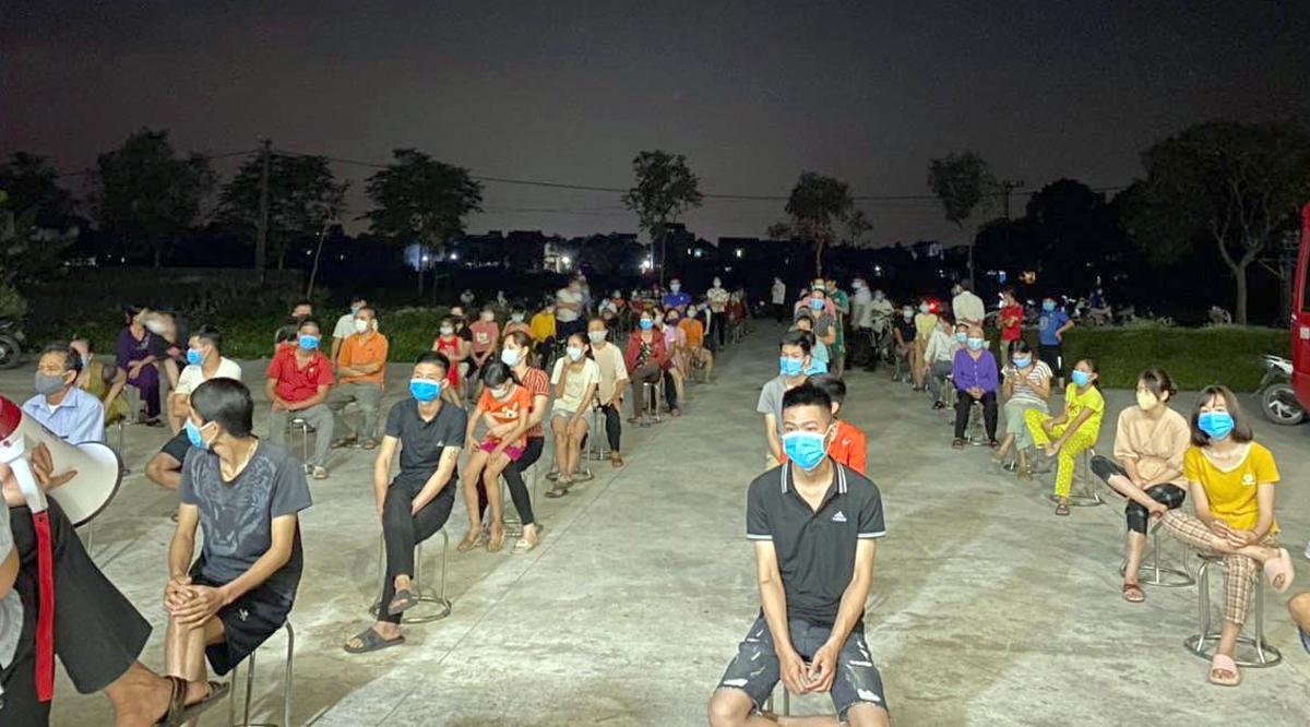 Người dân ở xã Mão Điền ngồi xếp hàng giãn cách để chờ lấy mẫu xét nghiệm tối 7/5. Ảnh: CTV