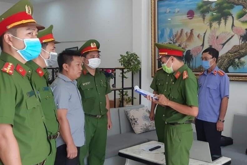 Cảnh sát đọc lệnh bắt tạm giam Cao Đức Trung. Ảnh: Đức Huynh.