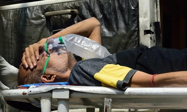Một bệnh nhân Covid-19 được chuyển tới bệnh viện trên cáng tại thành phố Kolkata, thủ phủ tỉnh Tây Bengal, Ấn Độ, ngày 24/4. Ảnh: Anadolu Agency.
